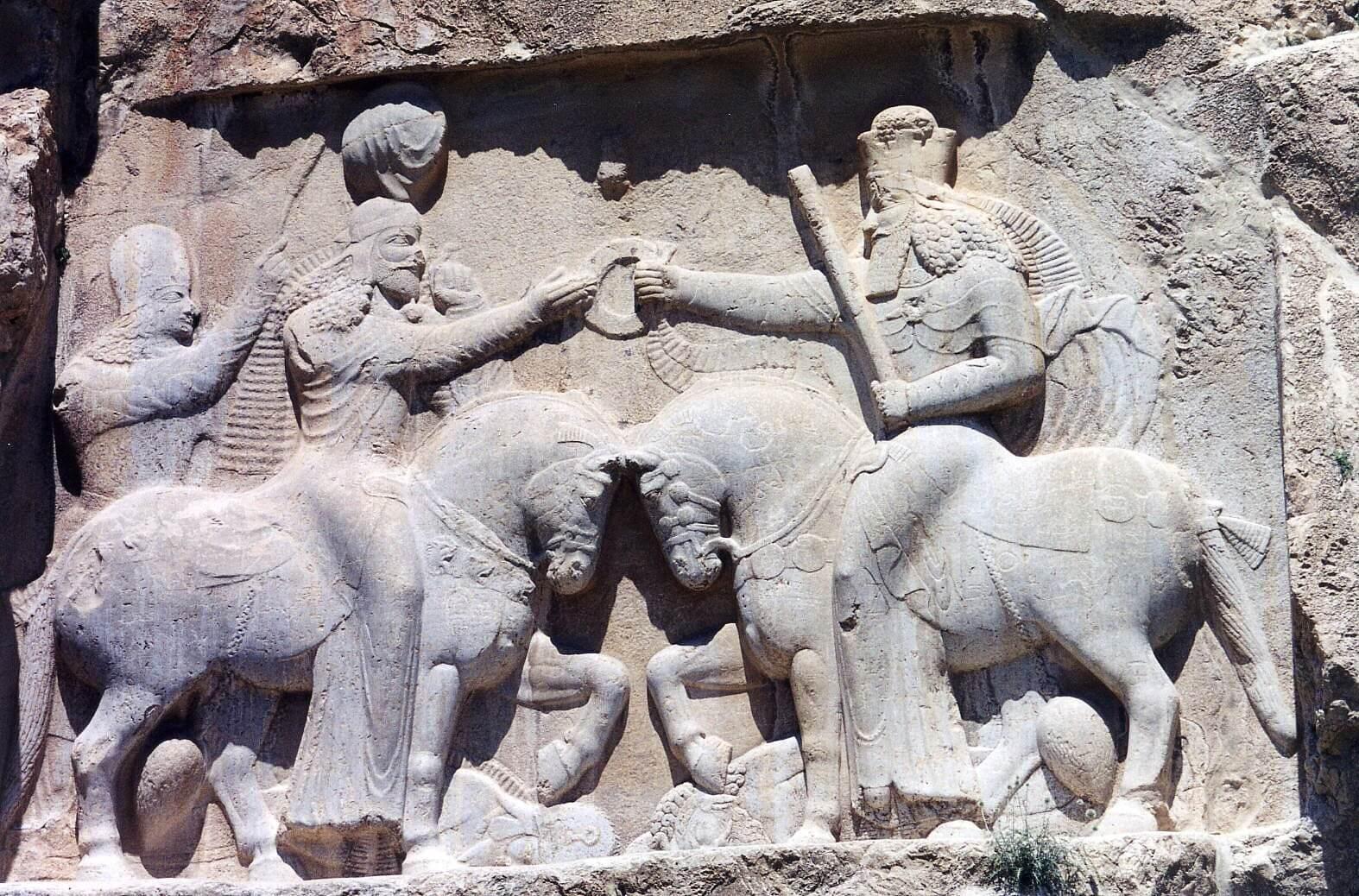 Ахура Мазда (справа) даёт Ардаширу символ царской власти — кольцо. III в. н. э. Накше-Рустам в 6 км к северу от Персеполя в Иране.