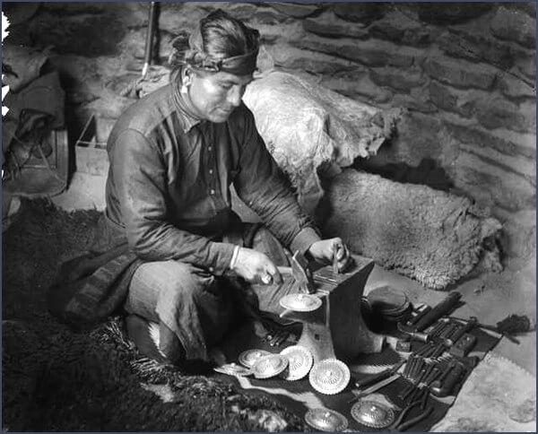 Один из серебряных дел мастеров племени Навахо штампует раковины на наковальне, чтобы использовать их в ювелирных изделиях, поясах или других украшениях, примерно в 1904-1932 годах. Серебряные и серебряно-бирюзовые украшения изготавливались как для личного пользования, так и для продажи на американском рынке.