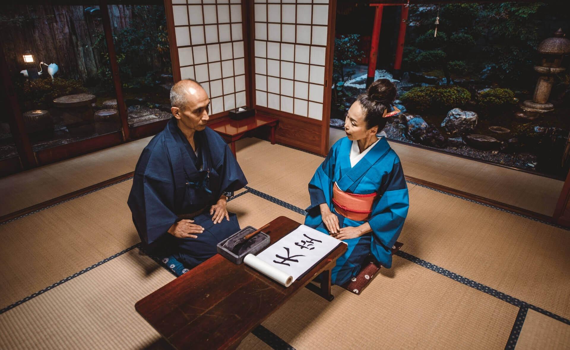 Семья японцев за занятием каллиграфией