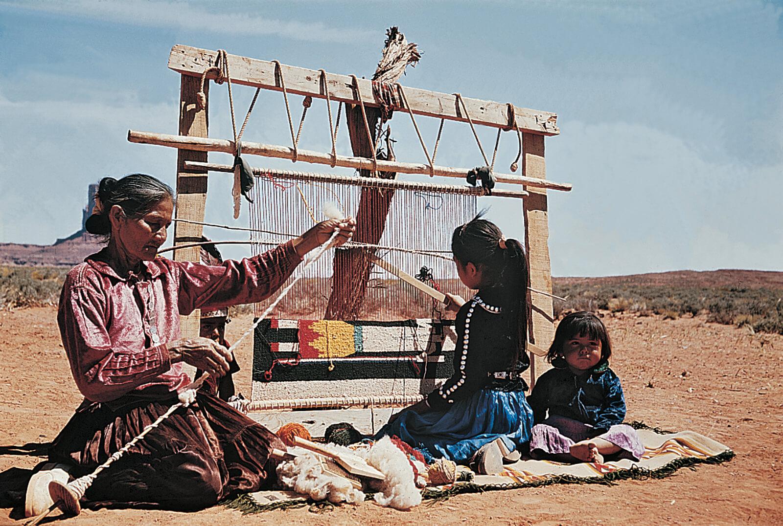 Женщина-Навахо, прядет пряжу, а девушка ткет ковер на станке.