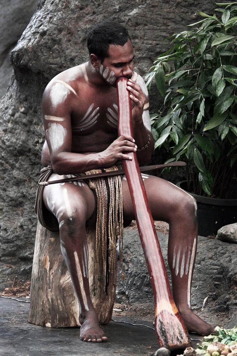 Играя на традиционном аборигенном музыкальном инструменте, диджериду