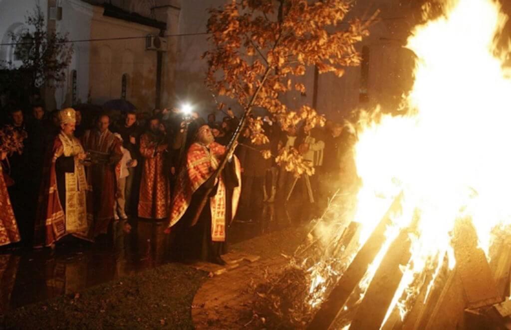 Сербский православный священник кладет бадняк в костер