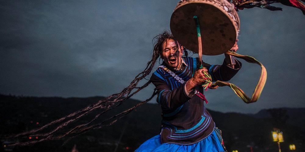 Шаман, одетый в традиционный костюм и, выступает на фестивале факелов в Сичане, китайская провинция Сычуань