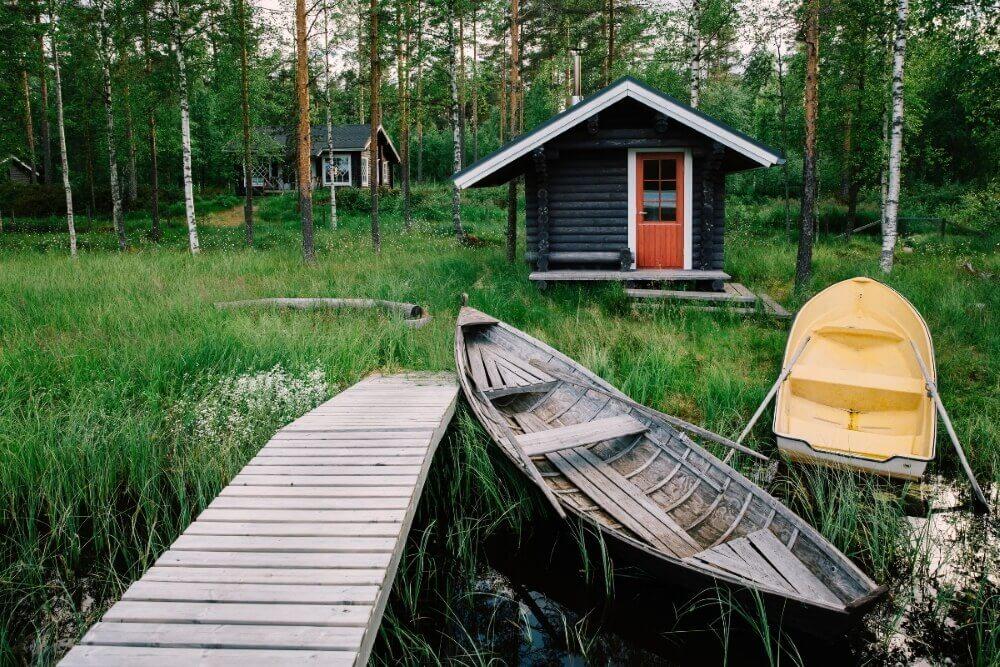 Традиционная деревянная хижина. Финская сауна на озере и пирс с рыбацкими лодками