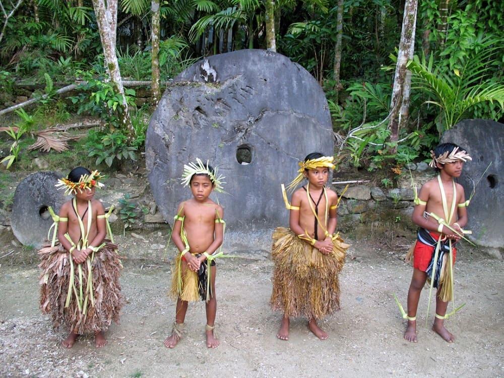 Микронезийские дети у каменных монет острова Яп