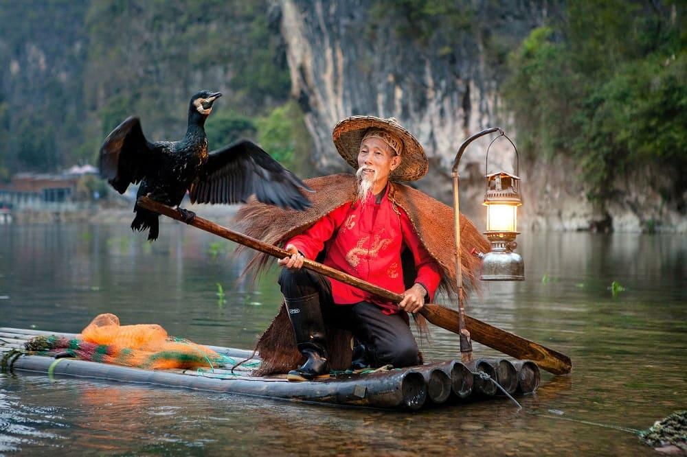 Фото рыбака с бакланом на реке Ли в Китае, окрестности Яншо / © Анна Заводчикова / nat-geo.ru